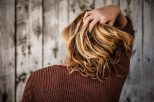 A person with head lice continues itching hair after DIY treatment.