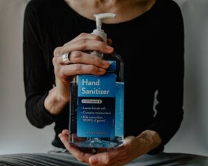 A person holds a bottle of hand-sanitizer for better hygiene.
